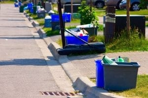 Recycling bins sit curbside on a residential street.