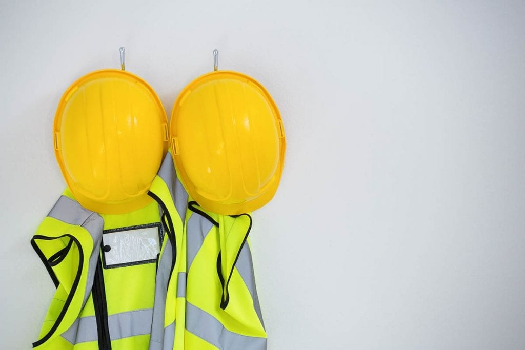 Safety vests and hard hats hanging on a wall.