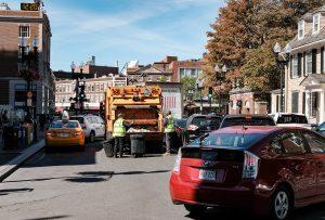 Waste collection truck on city street in Massachusetts.