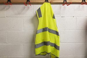 A yellow safety vest hanging at a workplace.
