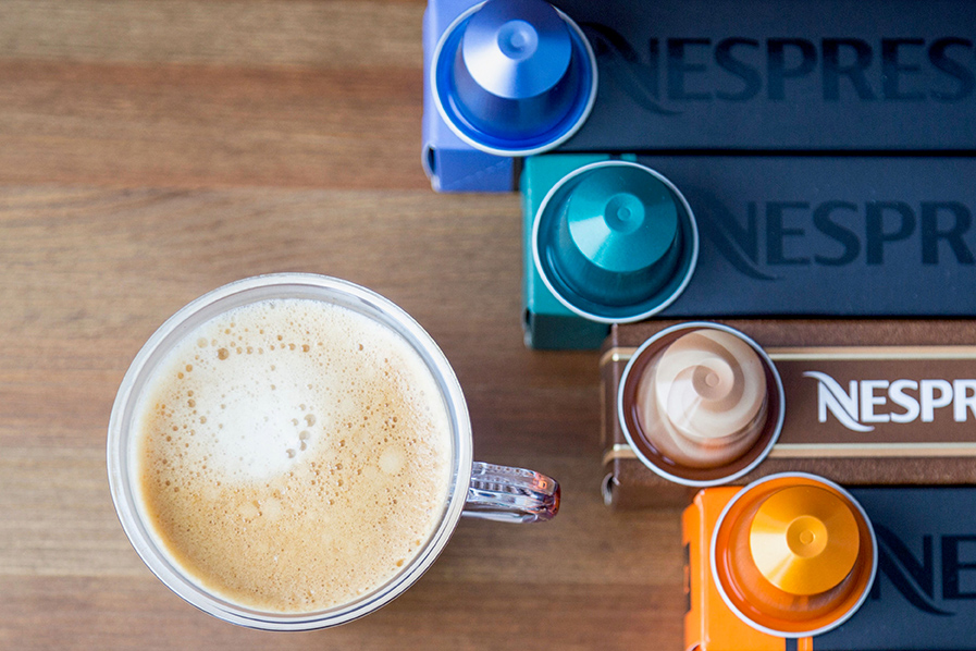 Cup of coffee with various Nespresso coffee capsules.
