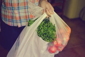 Person carrying vegetables in plastic bags.