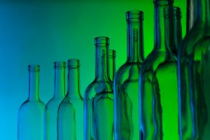 Glass bottles with a blue and green lit background.