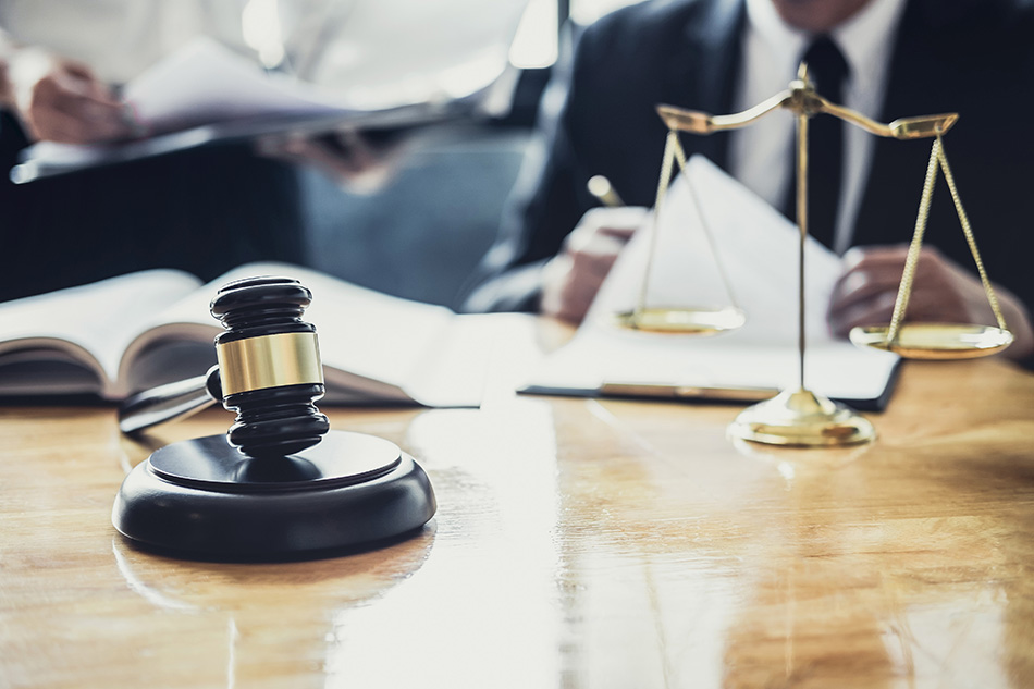 Court gavel and justice scales on a table.