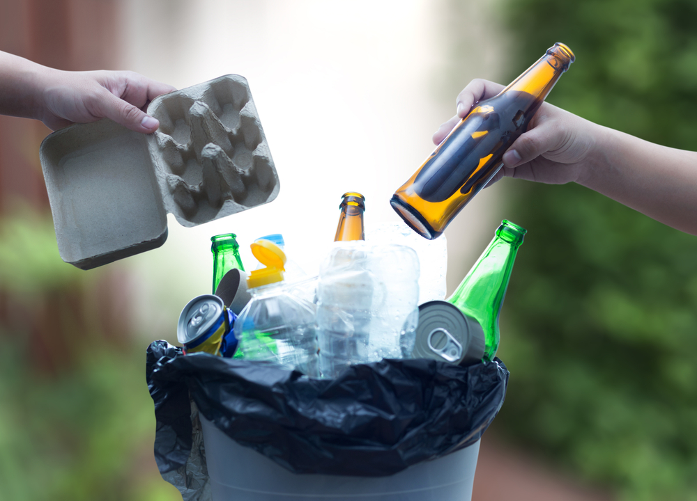 Handing materials into a recycling bin.