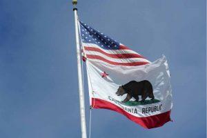 U.S. and California flags against a blue sky.