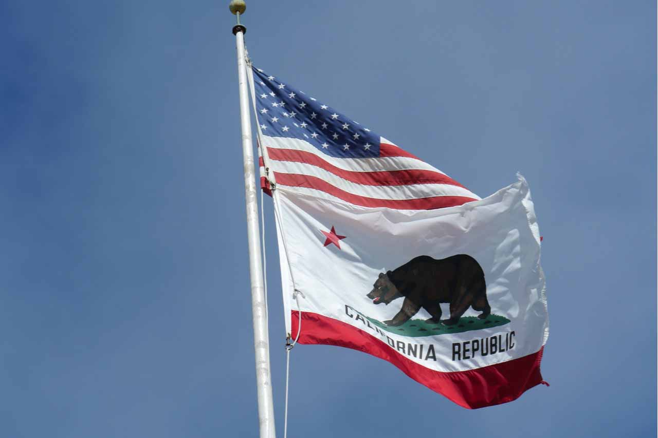 U.S. and California flags against a blue sky.