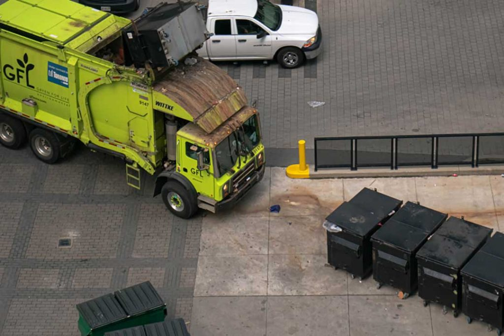 GFL truck collecting material from bins.