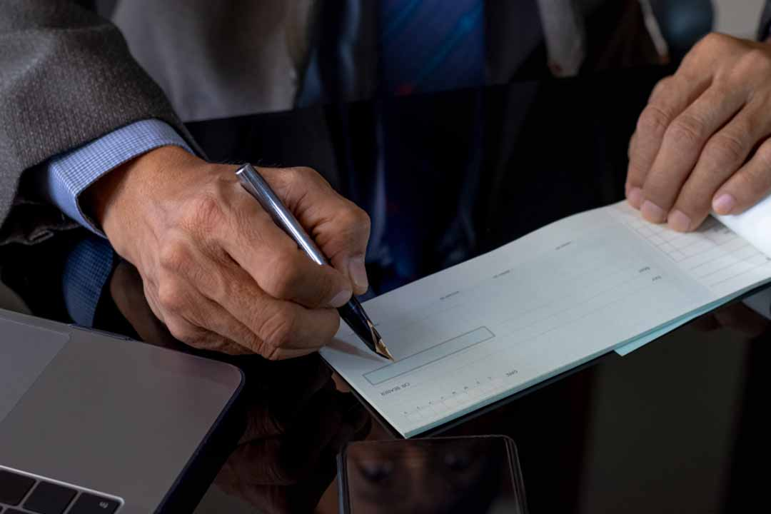 Person in a suit signing a check.