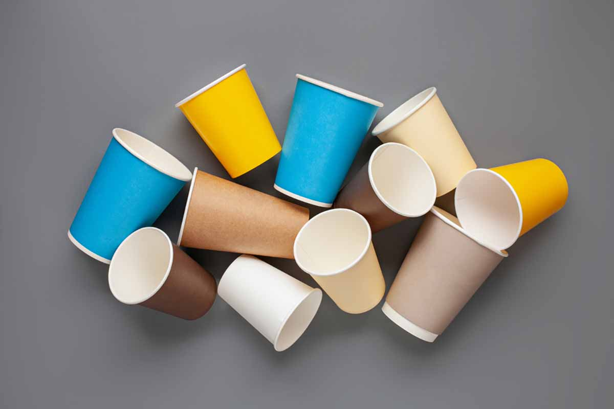 Colorful paper coffee cups on a gray background.