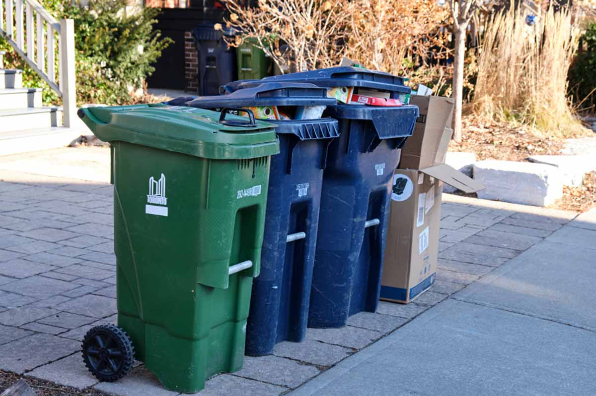 Recycling and waste carts on a curb in Toronto.