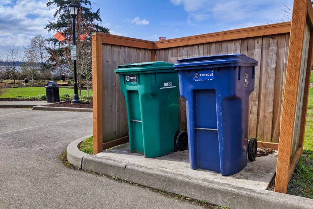 Residential waste and recycling bins on a curb.