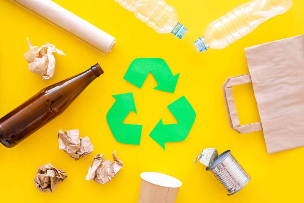 Mixed recyclables arranged around a recycle symbol.
