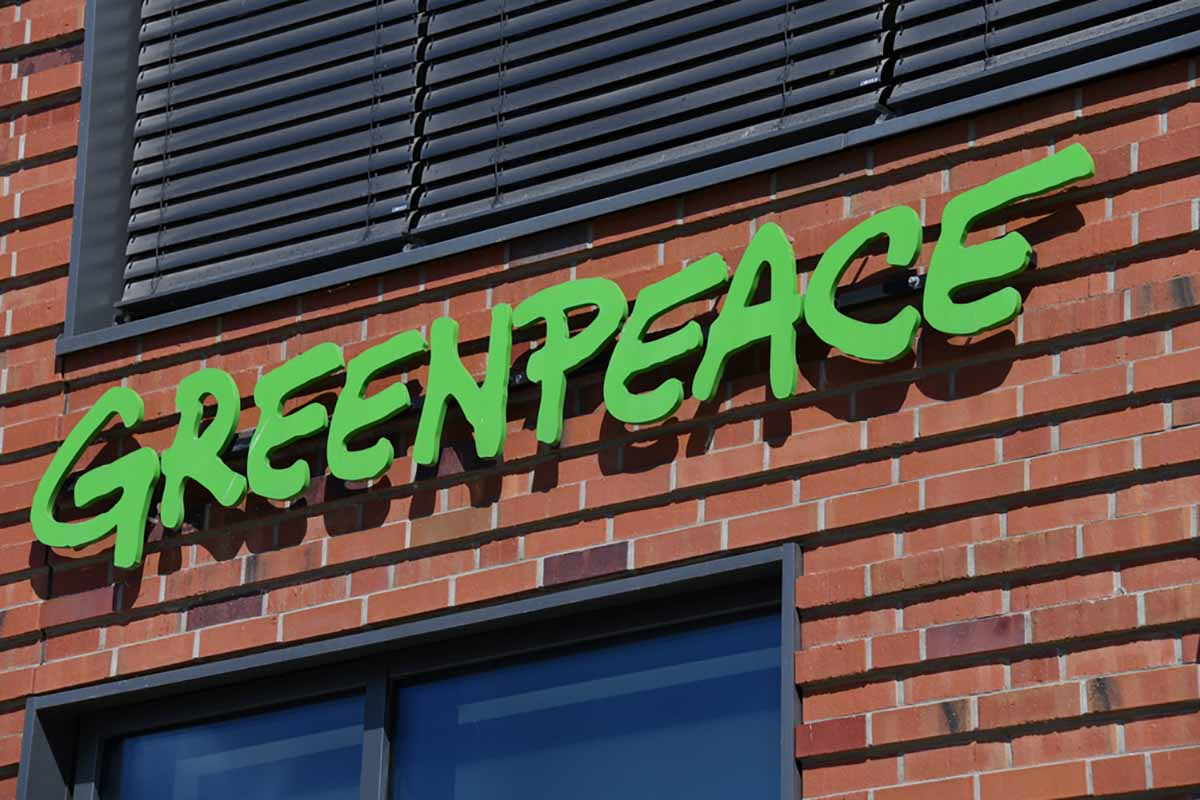 Greenpeace sign on a brick building exterior.