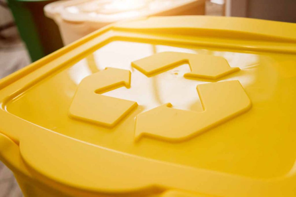 Yellow recycle container with chasing arrows symbol.