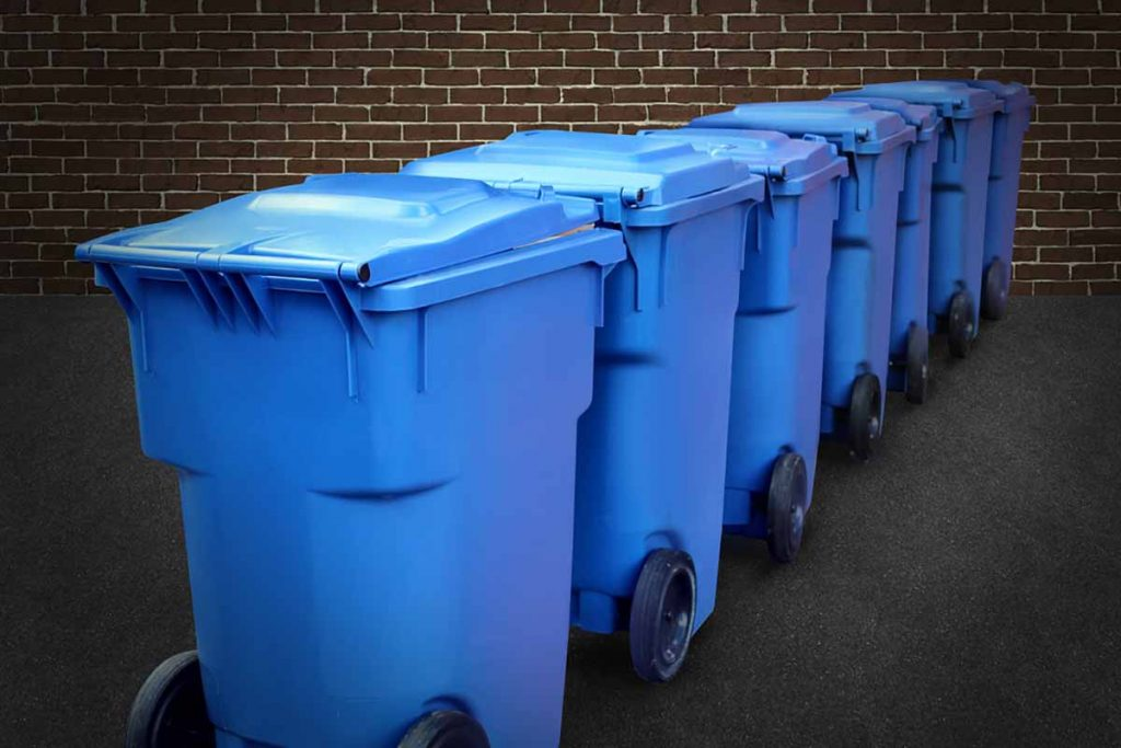 Blue recycling bins lined up against a brick background.