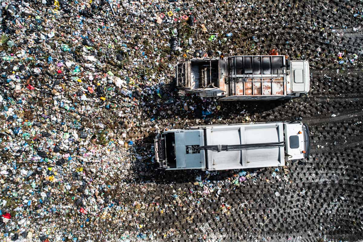 Trucks at a landfill site from above.