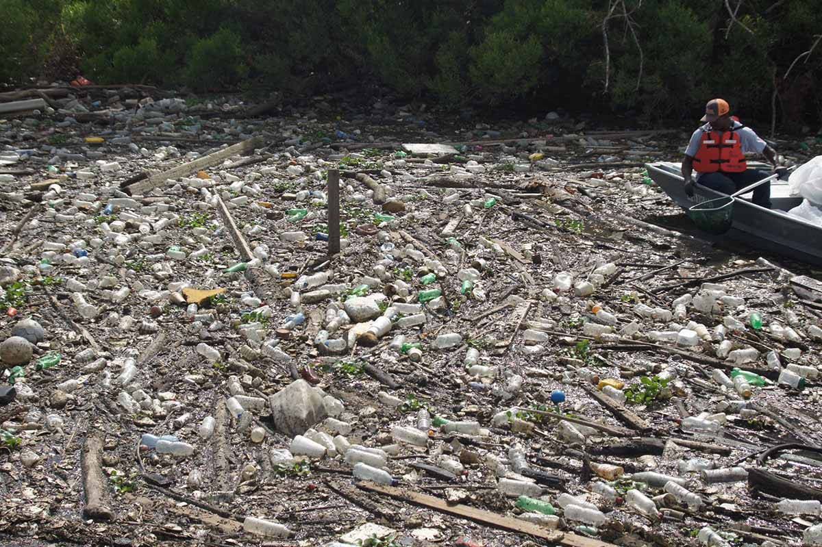 Crews remove plastic litter from Hunting Bayou in the Houston area.