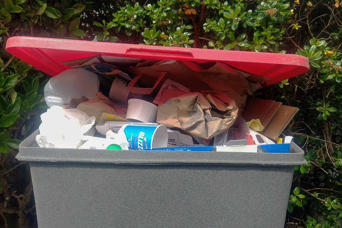 Recycling bin with some contamination from non-recyclable materials.
