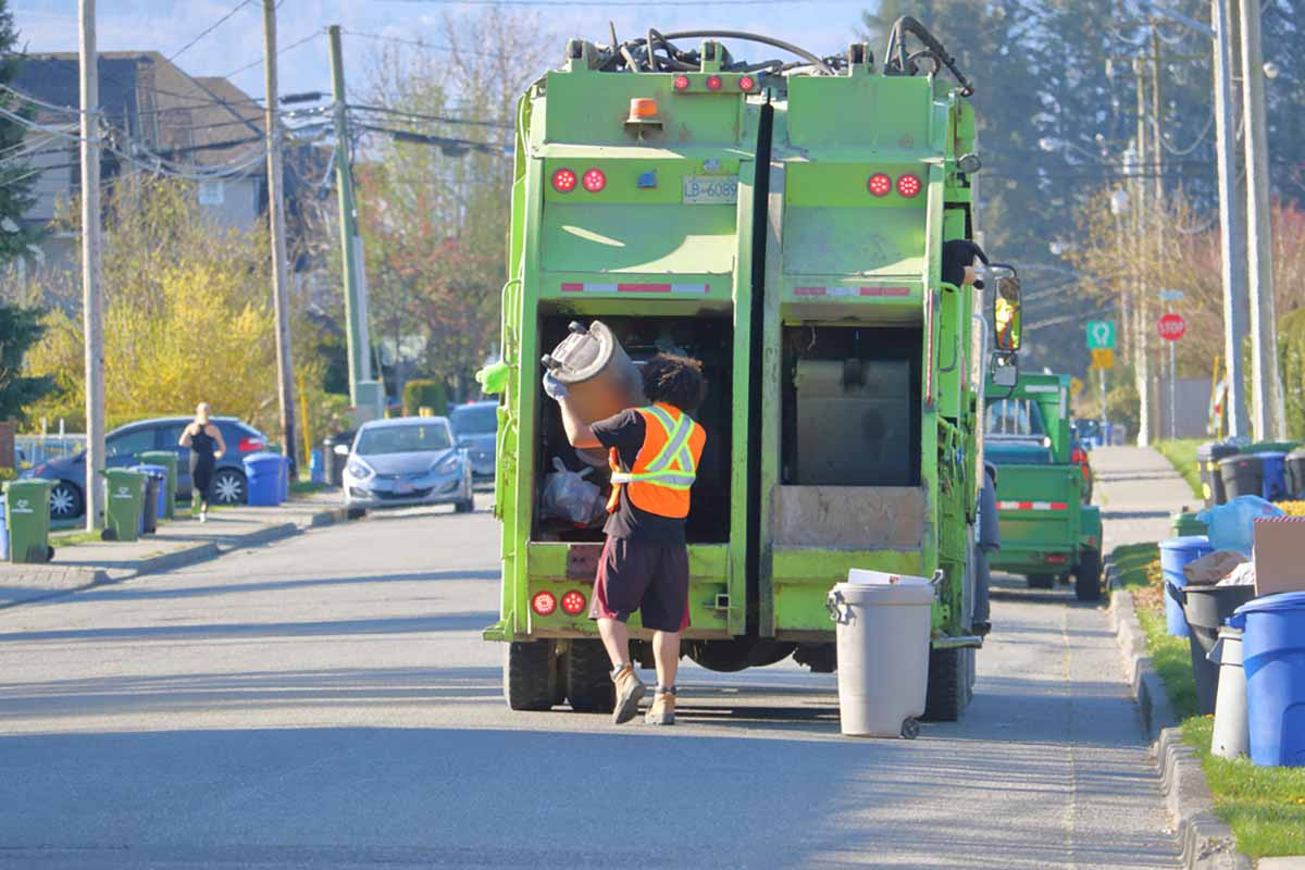 Worker unloads waste bin into collection truck on a residential street.
