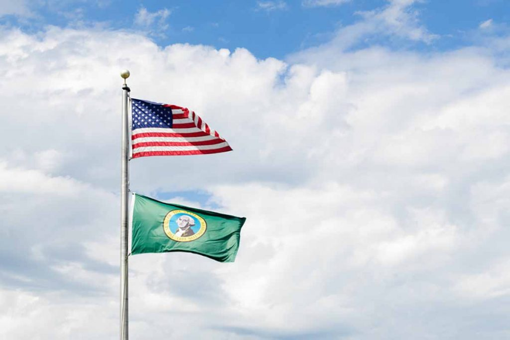 Flags of Washington state and the United States flying against clouds and blue sky.