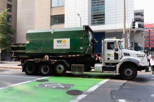 WM truck on a city street.