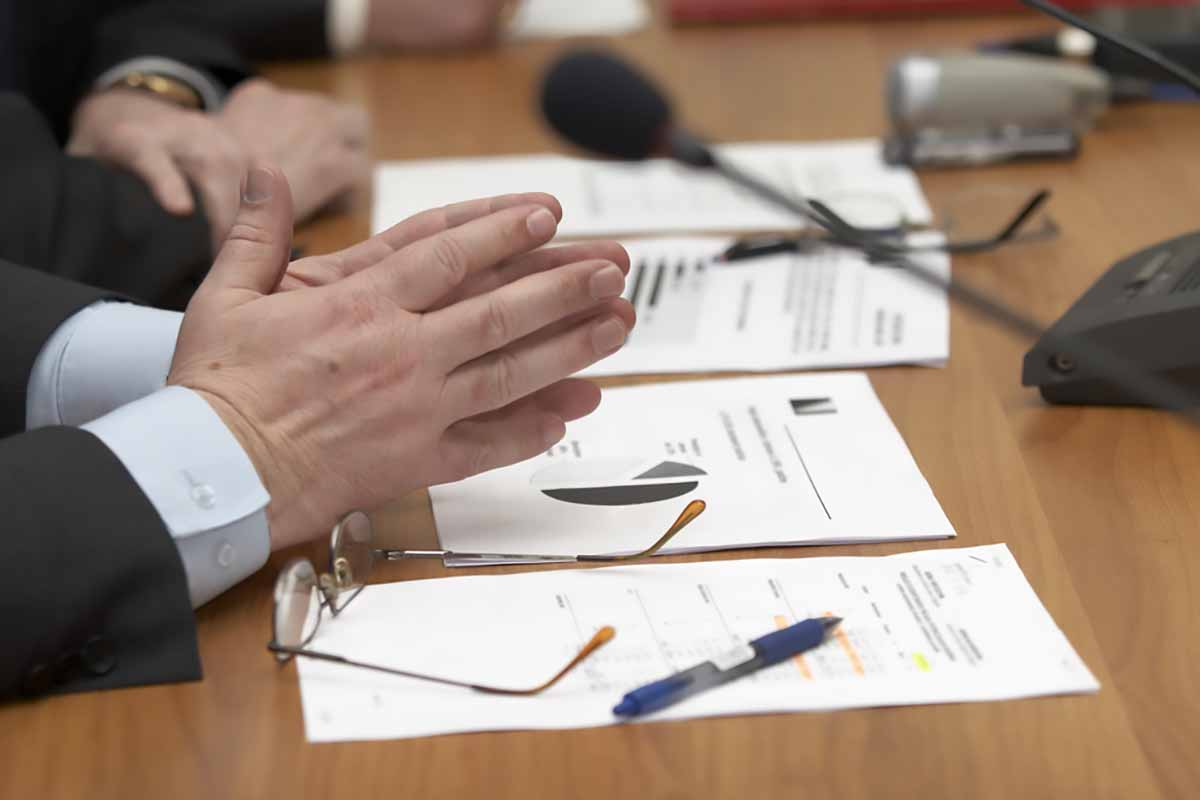 Close up of a meeting with microphone and papers on the desk.