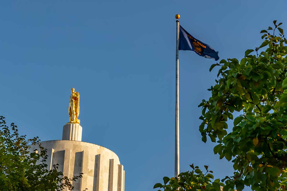 Oregon state capitol building with state flag and blue sky.