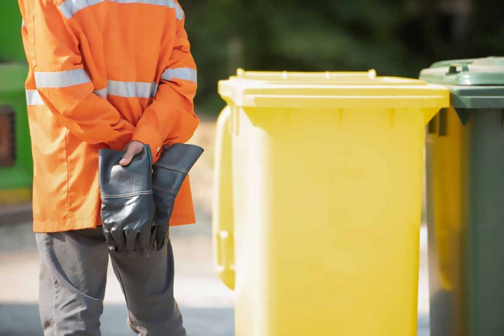 Municipal waste and recycling collection worker with bins.